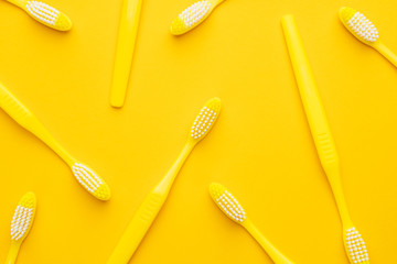 many new plastic toothbrushes on the yellow background