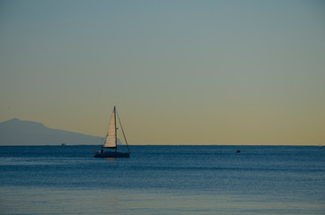 Sail boat on Capri Island silhouette background on amazing colorful sunset time. View from the coast of Naples,Italy .Tourism in Europe
