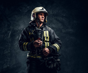 Studio portrait in a dark studio against a textured wall. Brutal firefighter in uniform and safety helmet holding an oxygen mask and looking sideways with a confident look.
