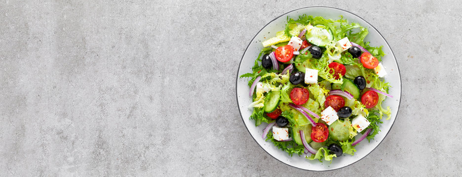Vegetable salad with fresh cucumber, tomato, olive, onion, lettuce and feta cheese. Healthy food. Top view. Banner.