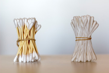 Bamboo cotton swabs and plastic cotton swabs over wooden table