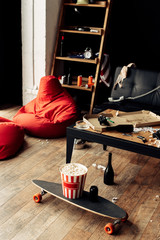 skateboard with popcorn box near coffee table in messy living room
