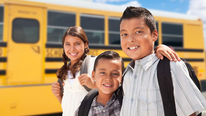 Young Hispanic Boys and Girl Walking Near School Bus