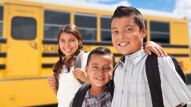 Young Hispanic Boys and Girl Walking Near School Bus