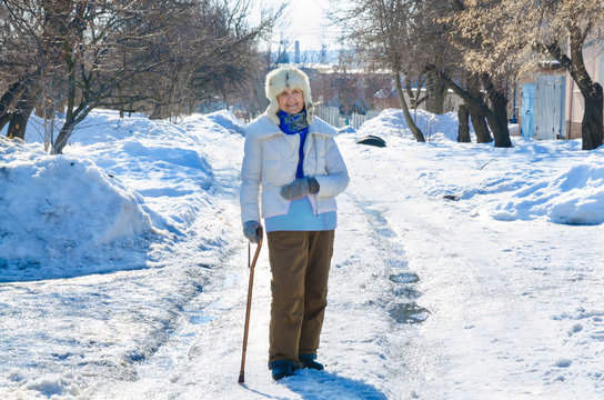 grandmother with cane on road in park . old person leaning on a walking stick. caucasian female senior at cold winter. fashion lady outside. healthy leisure of grandma in fur hat. elderly stay on snow