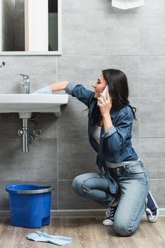 Smiling woman talking on phone while repairing faucet
