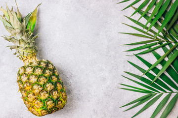 Pineapples and tropical palm leaves on light concrete background.