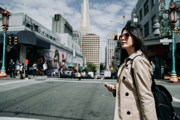 pretty cool smiling young asian woman using smartphone walking in city san francisco. happy female model wearing elegant sunglasses outdoors sightseeing in chinatown. Transamerica Pyramid in back.