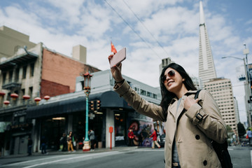 young girl taking selfie standing on road in chinatown. female asian travel backpacker holding cellphone make self portrait with Transamerica Pyramid tower building in san francisco in usa.