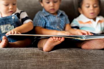 Three little boys reading a book on a sofa