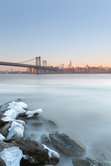 Williamsburg bridge and Downtown Manhattan view from east river beach at sunrise with long exposure
