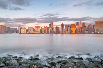 Midtown Manhattan view from east river beach at sunrise with long exposure