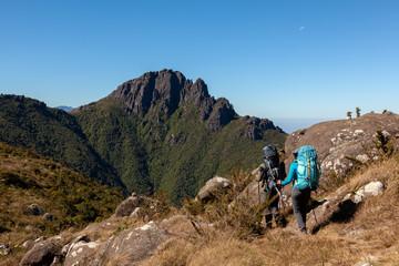 People walking with great backpacks in mountain landscape - trekking hiking mountaneering in mantiqueira range Brazil
