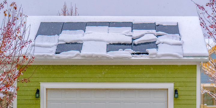 Solar panels on snow covered roof in winter