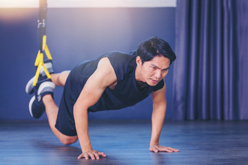Fit man doing plank exercise for back spine by push ups with TRX fitness straps in the gym