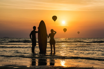 Silhouette of Surfer man and younger sister standing happily and enjoy on the beach looking out to hot air balloon over the sea with surfboards in the sunset after surfing.