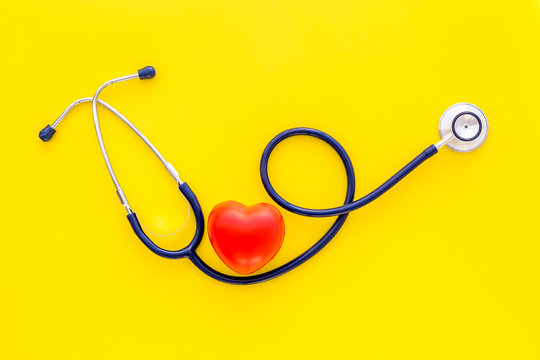 Heart health, health care concept. Stethoscope near rubber heart on yellow background top view copy space