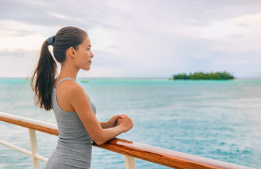 Wall Mural - Cruise ship luxury Tahiti vacation island hopping French Polynesia Oceania world tour in yacht on tropical ocean travel - Young tourist Asian woman watching sunset on deck of cruising boat.