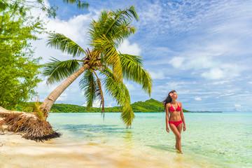 Tahiti luxury beach bikini Asian woman relaxing on French Polynesia cruise ship travel Bora Bora vacation beautiful swimsuit enjoying sun tan on polynesian island.