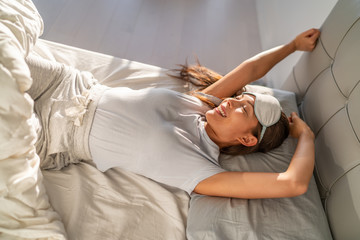 Morning woman waking up happy stretching in bed with sleeping eye mask. Healthy home lifestyle Asian girl feeling rested on organic mattress.