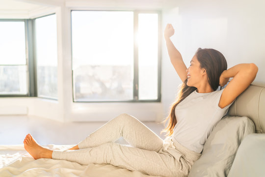 Morning woman waking up stretching in bed in sunshine sunrise early bird happy Asian girl in pajamas on weekend in sun glow. Healthy wake-up routine home lifestyle.