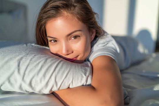 Beautiful Asian woman relaxing at home on pillow bed in bedroom candid smiling portrait. Natural beauty healthy skin model face.