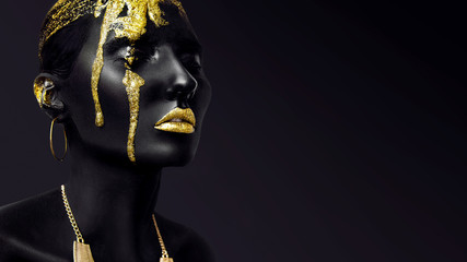 Foto op Plexiglas Fashion Lips Young woman face with art fashion gold makeup. An amazing model with black and yellow creative makeup. Closeup portrait