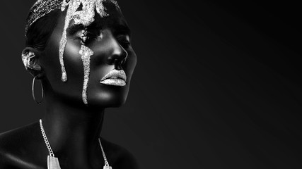 Young woman face with art fashion makeup. An amazing model with creative makeup. Black skin, Black and white closeup portrait