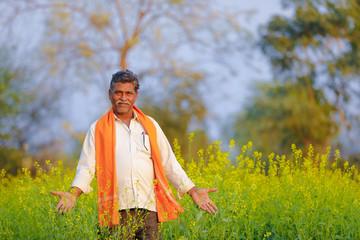 Indian farmer at black mustard field