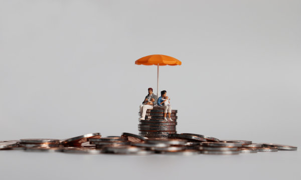 A miniature couple holding a baby sitting with an orange umbrella on a pile of coins.
