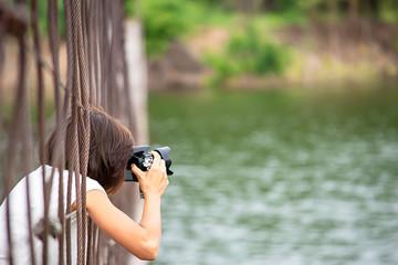 Hand woman holding the camera Taking pictures on  wooden bridge Background Kaeng Krachan dam phetchaburi , Thailand.