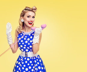 smiling woman with phone, dressed in pin-up style
