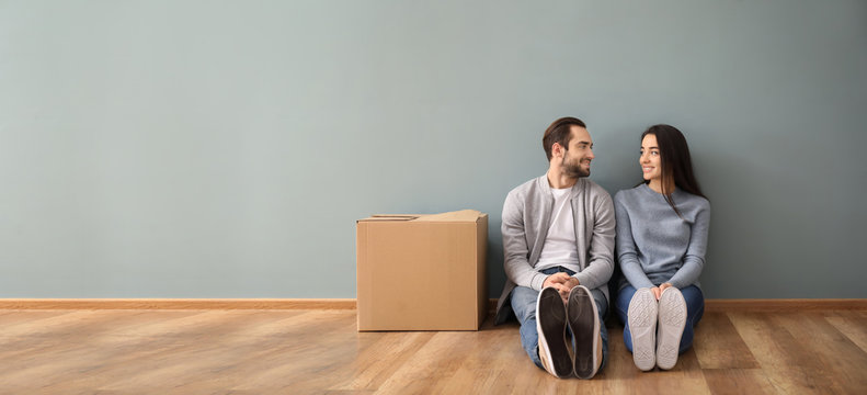 Young couple sitting on floor near box indoors. Moving into new house
