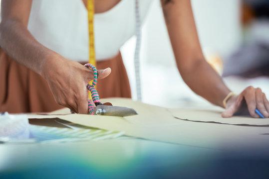 Seamstress cutting paper pattern