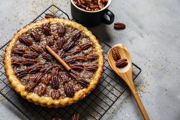 Cooling rack with tasty pecan pie on grey table
