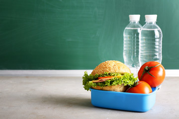 School lunch box with tasty food and bottles of water on table