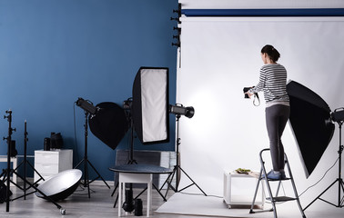 Young woman taking picture of food in professional studio