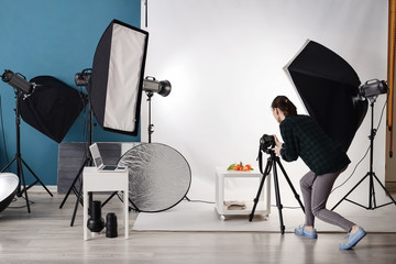 Young woman taking picture of fresh tangerines in professional studio
