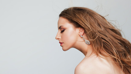 Portrait of a beautiful young woman with flying curls. Girl with beautiful earrings