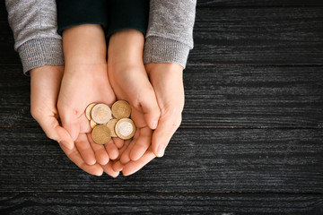 Hands of woman and his son holding coins on wooden table. Concept of child support