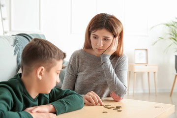Sad mother with son counting alimony at home