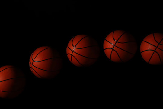 Stroboscopic photo of moving ball on dark background