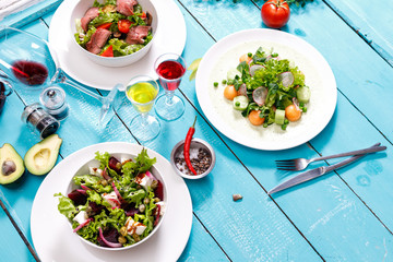 Greek salad background. Bowl with fresh greek salad, tomatoes, olives, olive oil on wooden table. Space for text. Top view. Traditional greek dish. Ingredients for making salad. Mediterranean diet