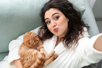 Young woman taking selfie with cute funny cat at home