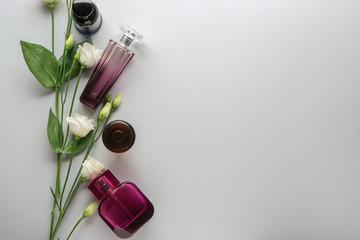 Bottles of perfume and flowers on light background Fototapete