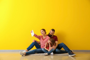 Happy family taking selfie while sitting on floor in their new flat