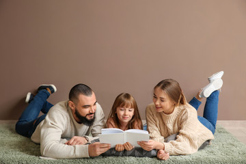 Happy family reading book on carpet near color wall