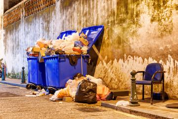 Overflowed garbage bins and old chair