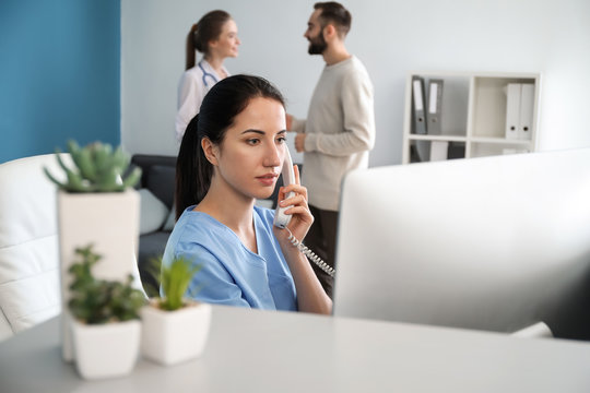 Female receptionist talking by phone in clinic