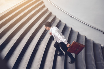 Businessman walking up on stairs and holding suitcase.